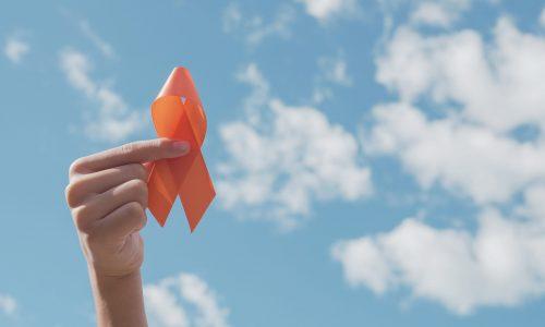 hands-holding-orange-ribbon-over-blue-sky-min